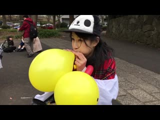 Japanese girl blows up a yellow balloon and bites it till it pops