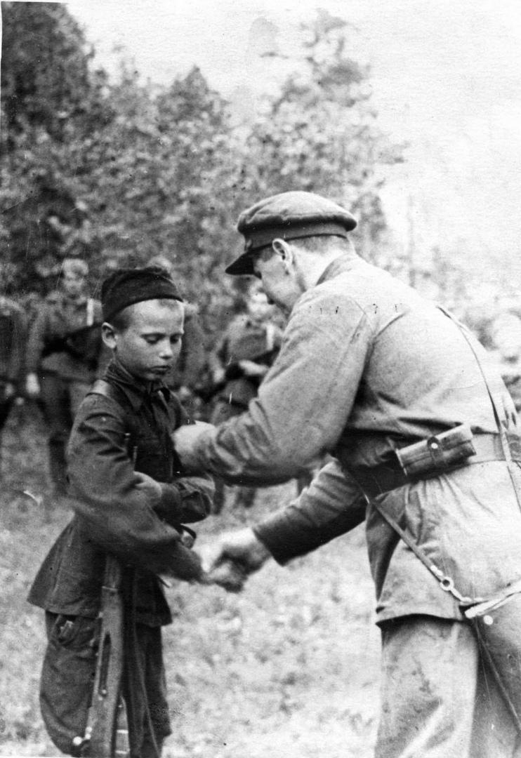 30 июля 1942 года. Командир партизанского отряда вручает медаль «За отвагу» юном...
