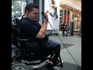 Парень в инвалидном кресле тренируется в зале не смотря ни на что