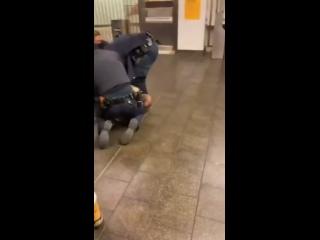 Задержание темнокожего мужчины в метро Нью-Йорка — трое полицейских его держат, четвёртый бьёт по голове